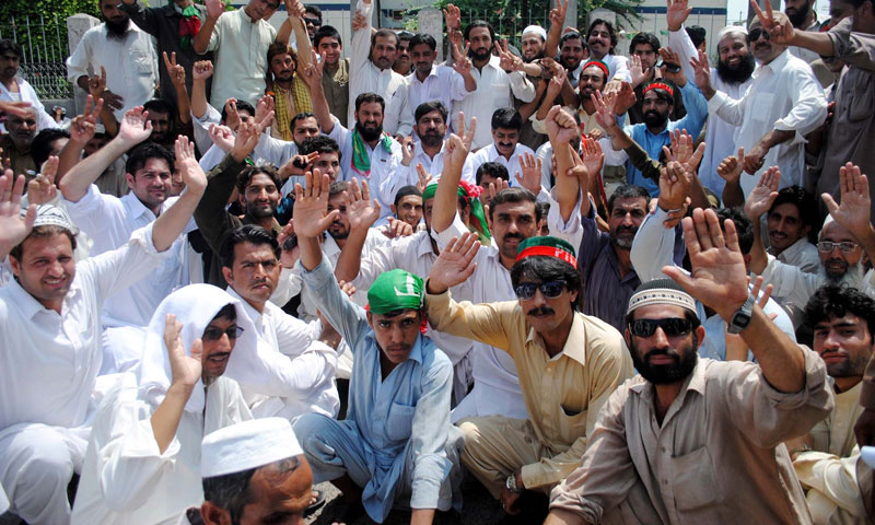 Leaders and activists of Pakistan Tehreek-i-Insaf chant slogans against Water and Power Development Authority (WAPDA) department during protest demonstration at Peshawar Press Club. — Photo by PPI