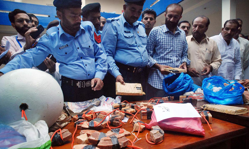 Policemen show explosives and detonators which were found from a car impounded by police at Bhara Kahu. — Online photo