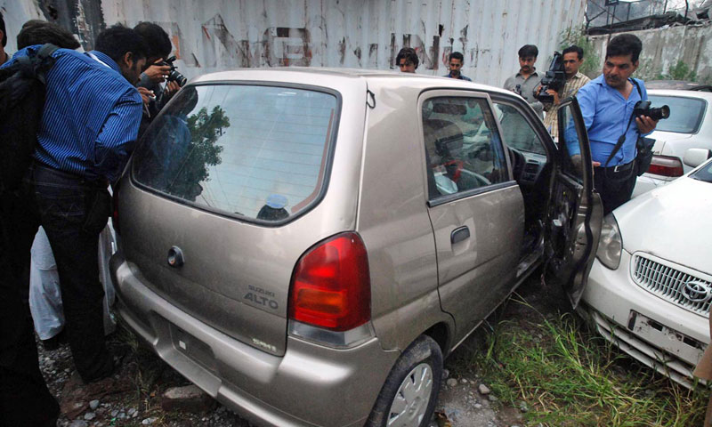 Photojournalists take pictures of a car which was impounded by police after they found explosives and detonators inside it. — Online photo