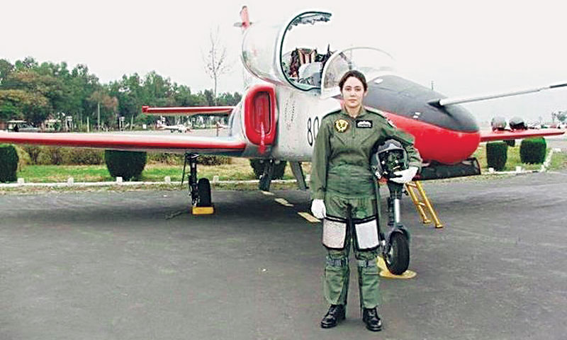 Female Pilot of Pakistan Air Force Ambreen Gul standing with plane during training.