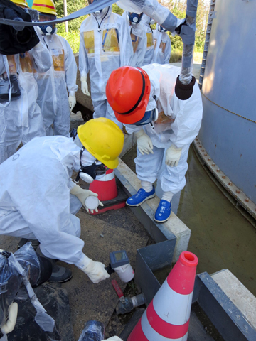 This handout picture taken by Tokyo Electric Power Co. (TEPCO) on August 26, 2013 and received on September 1, 2013 shows Japanese Economy, Trade and Industry Minister Toshimitsu Motegi (R-red helmet) inspecting contamination water tanks at TEPCO's Fukushima Dai-ichi nuclear power plant in the town of Okuma, Fukushima prefecture.  TEPCO said on August 31 it had found new radiation hotspots near tanks storing toxic water, with one reading peaking at 1,800 millisieverts per hour - a potentially lethal dose. — AFP Pho