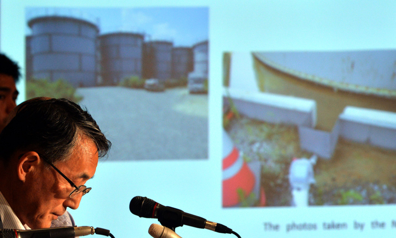 Nuclear Regulation Authority chairman Shunichi Tanaka (L) delivers a speech while pictures of the Fukushima Dai-ichi nuclear plant's water tanks is displayed during a press conference at the Foreign Correspondents' Club in Tokyo on September 2, 2013. Japan's nuclear watchdog chief said on September 2 that contaminated water from the ruined Fukushima nuclear plant must be released into the ocean eventually, warning the plant remains fragile with many risks. — AFP Photo