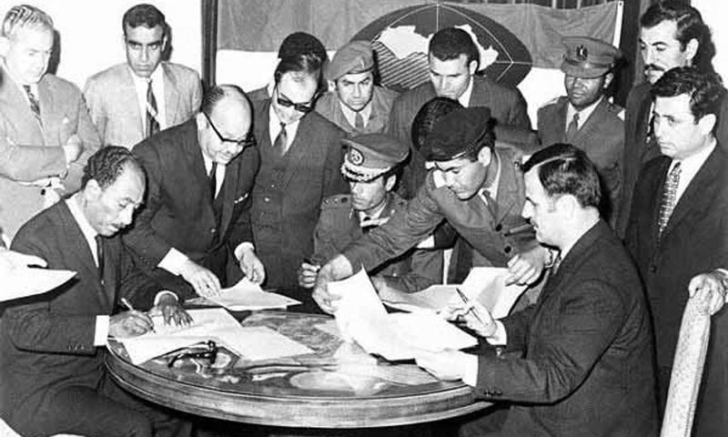Syria's President Hafez al-Asad (sitting on the right side) signing the Federation of Arab Republics in Benghazi, Libya, on April 18, 1971 with President Anwar al-Sadat (sitting left) of Egypt and Colonel Muammar al-Qaddafi of Libya (sitting in the centre). The agreement never materialised into a federal union between the three Arab states. -Source: The Online Museum of Syrian History