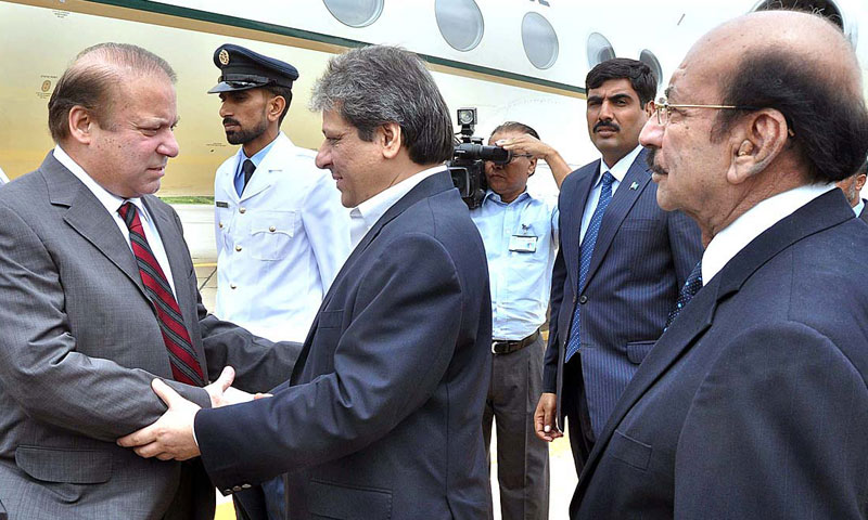 Governor Sindh Ishratul Ibad and Chief Minister Qaim Ali Shah receiving the prime minister on his arrival in Karachi.— Photo by APP