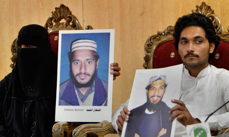 Fatima Bibi, left, and Fazal Naeem show pictures of their family members who are held by the US at a prison in Afghanistan during a press conference in Islamabad, Pakistan, Wednesday, Sept. 4, 2013. –AP Photo