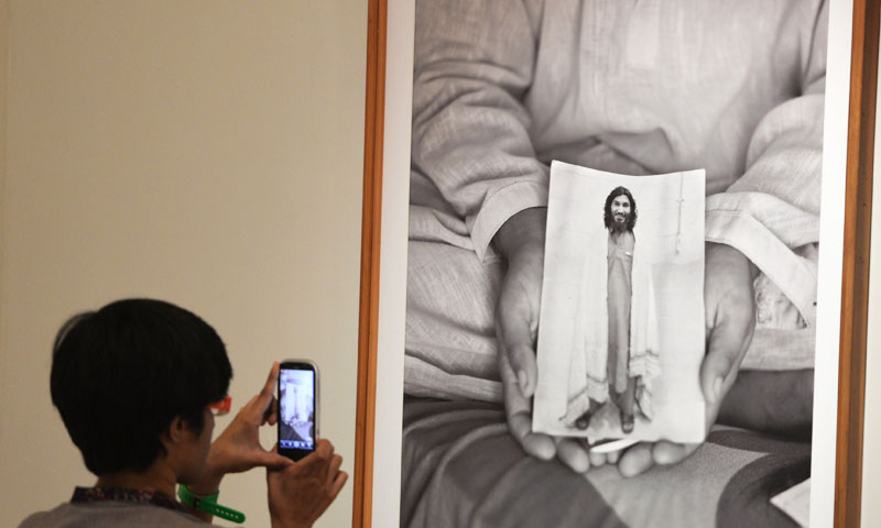 A visitor takes pictures of a photograph showing a relative holding the portrait of a prisoner  currently under detention by the US at the Bagram prison in Afghanistan. -Photo by AFP