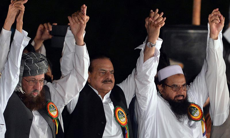 Hafiz Saeed (R), former Pakistani intelligence ISI chief Hamid Gul (C), and Chairman of the Defence of Pakistan coalition Maulana Sami ul-Haq (L) join hands as they attend an anti-India rally in Islamabad. -AFP Photo