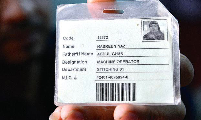 Mohammad Babar show the employee card of his wife, Nasreen Naz, who was killed in the fire. The factory's name is not mentioned on the card. -Photo by White Star