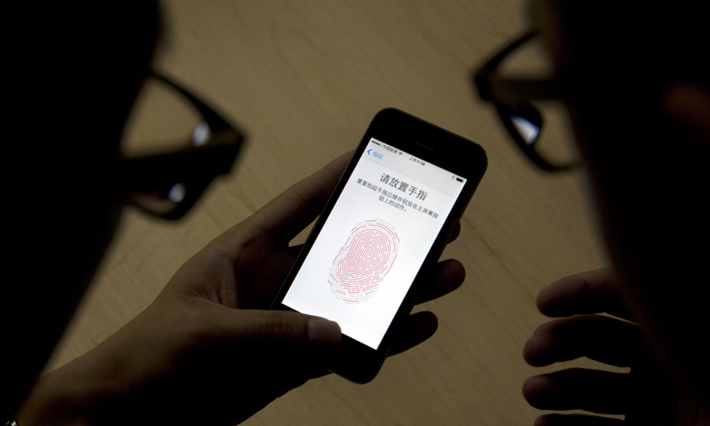 "An Apple employee, right, instructs a journalist on the use of the fingerprint scanner technology built into the company's iPhone 5S during a media event held in Beijing, China, Wednesday, Sept. 11, 2013. For the first time since introducing the device that has reshaped technology and culture, Apple will offer two distinct versions of its latest iPhones - a cheaper model made of colorful plastic and another one that aims to be ""the gold standard of smartphones"" with a faster processor, fancier camera and fingerprin"