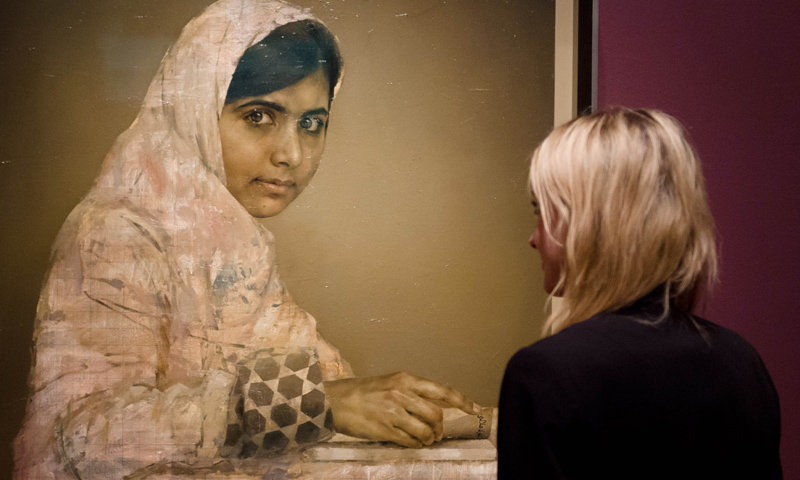 A gallery worker poses with a portrait of Malala Yousafzai by Jonathan Yeo at the National Portrait Gallery in central London on September 10, 2013. -Photo by AFP