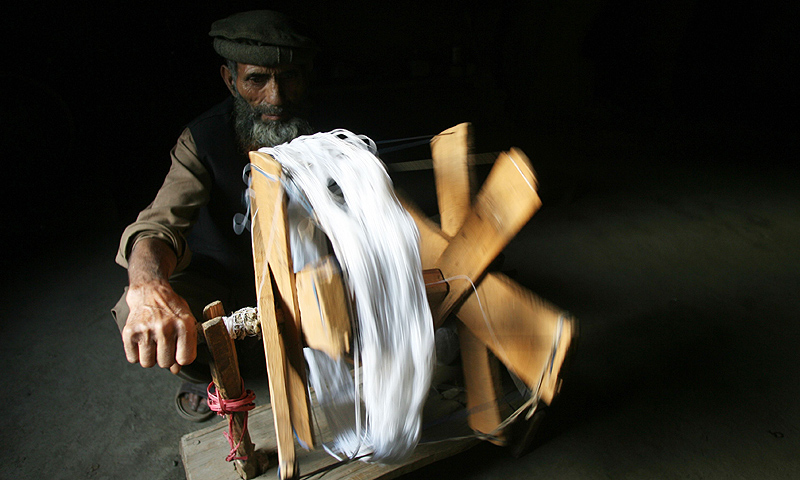 Wali Mohammad works a manuel spinning machine at his house high in the Grace Valley in Kashmir, some 175 kilometres from Muzaffarabad, the capital of Pakistan-administered Kashmir. -Photo by AFP