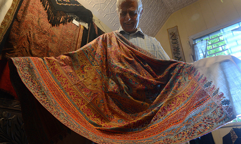 Mohammad Sadiq Wani, a seller of the finest Kashmir handicraft products displays a high quality hand-embroidered Pashmina shawl at his shop in Srinagar. -Photo by AFP