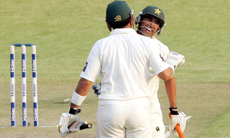 Younis Khan  is congratulated by captain Misbah-ul- Haq after Younis reached 7,000 Test runs. -Photo by AFP
