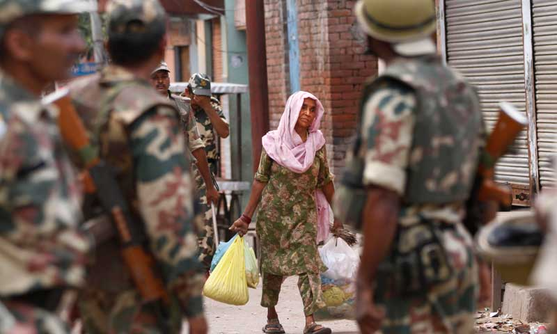 In this Monday, Sept. 9, 2013 photograph, Indian army soldiers patrol as a woman walks past during a curfew imposed following deadly clashes between Hindus and Muslims at Muzaffarnagar in Uttar Pradesh state, India. Violence has eased in an area of northern India battered by days of deadly clashes between Hindus and Muslims, with a massive deployment of security forces keeping most rioters off the streets, police said Tuesday. (AP Photo/ Rajesh Kumar Singh)