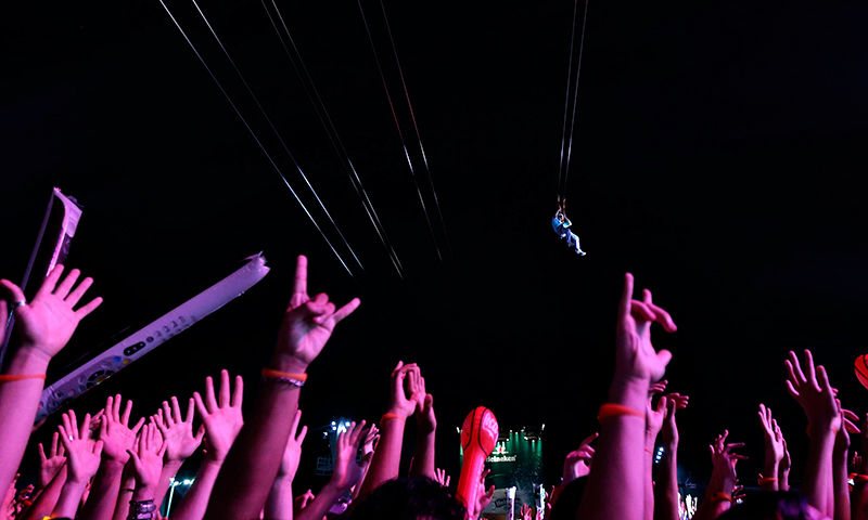 A fan slides down a zip-line as the audience attends a concert by Capital Inicial at the Rock in Rio Music Festival. - Photo by Reuters