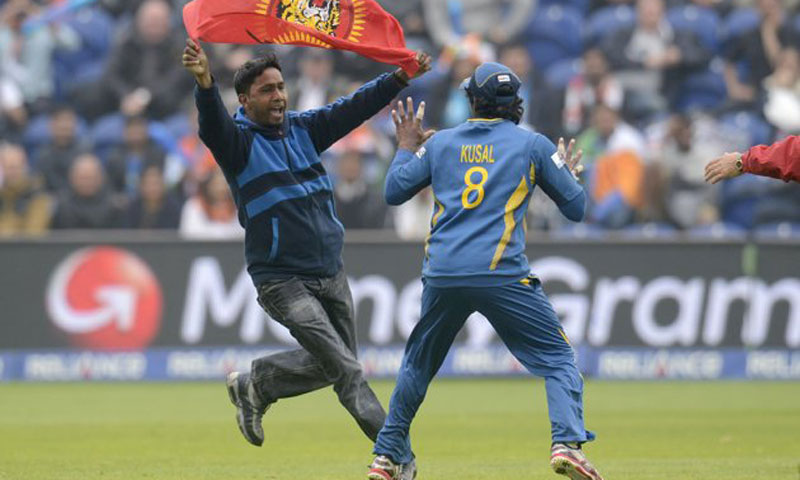 A Sri Lankan Tamil invades the ground with a Tamil Tigers' flag and runs towards a shocked Sri Lankan cricketer.