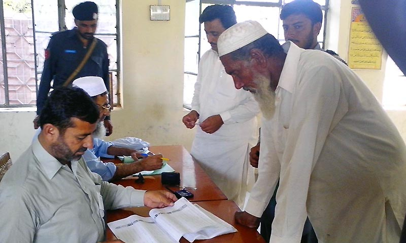 Polling staff busy in their work at a polling station during by-elections at NA-25.  — Photo by Online