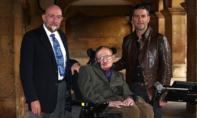 Theoretical physicist Stephen Hawking (C) poses for a picture with 'Hawking' director Stephen Finnigan (R) and Philip Martin (L), the director of a 2004 TV drama entitled 'Hawking', ahead of a gala screening of the documentary 'Hawking', a film about the scientist's life, at the opening night of the Cambridge Film Festival in Cambridge, eastern England on September 19, 2013. - Photo by AFP