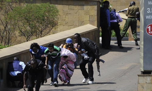 A policeman carry's a baby to safety after masked gunmen stormed an upmarket mall and sprayed gunfire on shoppers and staff, killing at least six on September 21, 2013 in Nairobi.—AFP Photo