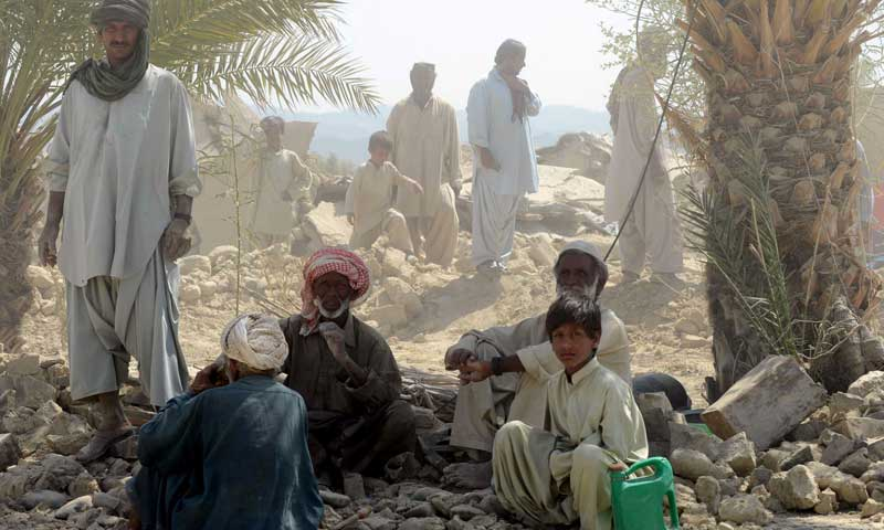 Survivors rest near their collapsed mud houses in the earthquake-devastated district of Awaran on September 25, 2013. — Photo by AFP