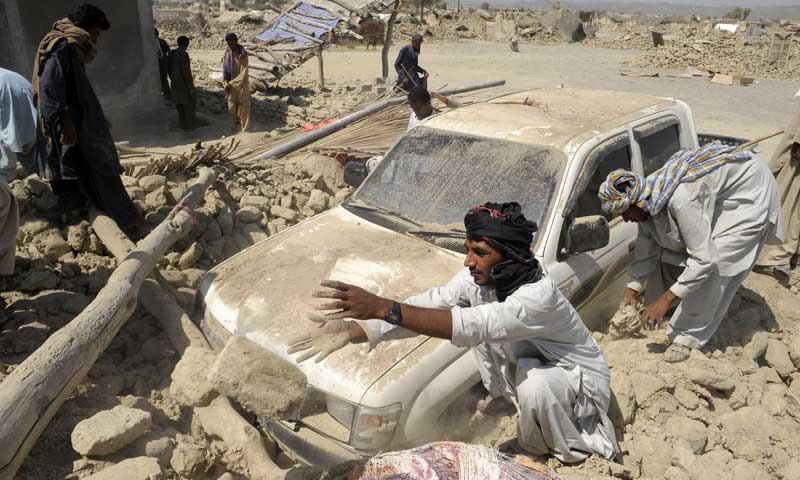 Survivors clear the debris of destroyed houses in the earthquake-devastated district of Awaran on September 25, 2013. — Photo by AFP