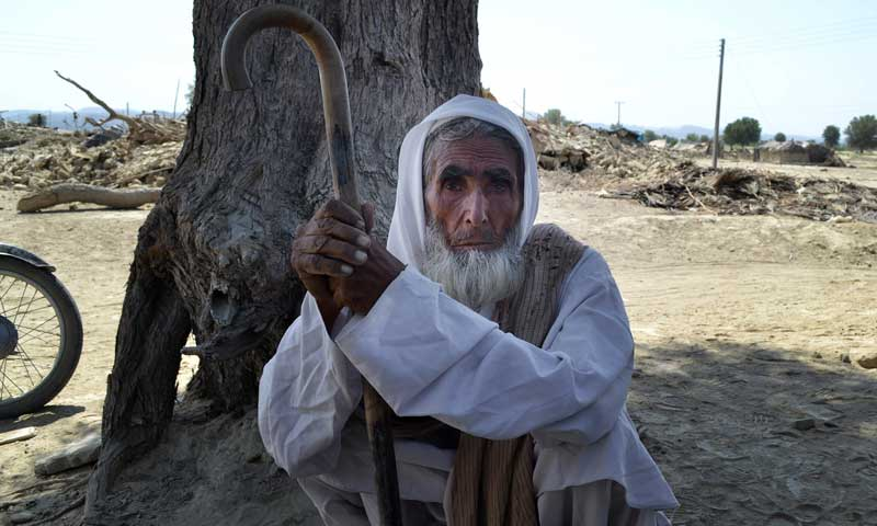 A villager rests under a tree near rubble of destroyed homes following an earthquake in the remote district of Awaran, September 25, 2013. — Photo by AP