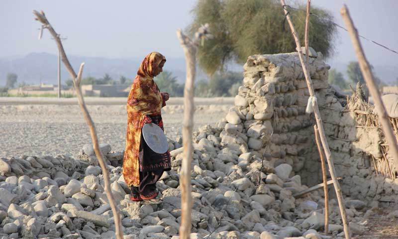 An earthquake survivor walks on the rubble of a mud house in the town of Awaran, September 27, 2013. — Photo by Reuters