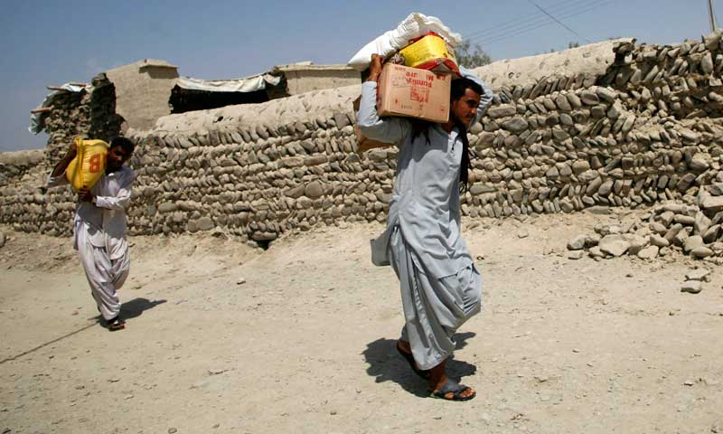 Earthquake survivors carry relief goods that were collected from a distribution point in the town of Awaran, September 26, 2013. — Photo by Reuters