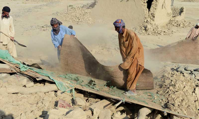 Earthquake survivors salvage their belongings in the rubble of a collapsed mud house in an area of the district of Awaran on September 27, 2013. — Photo by AFP