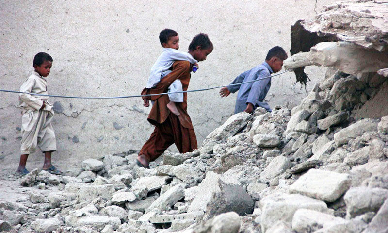 Survivors of the Awaran earthquake walk on the rubble of a mud house after. – Photo by Reuters