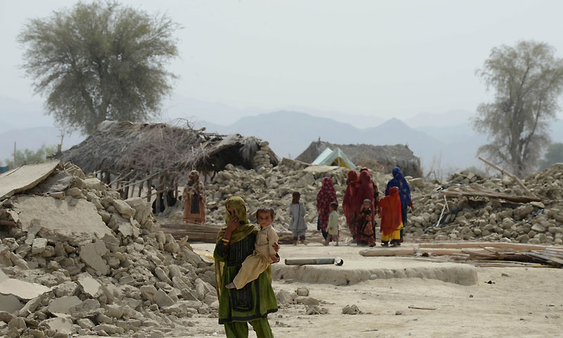 Earthquake survivors walk next to their destroyed houses in Peerander on September 29, 2013.— Photo by AFP