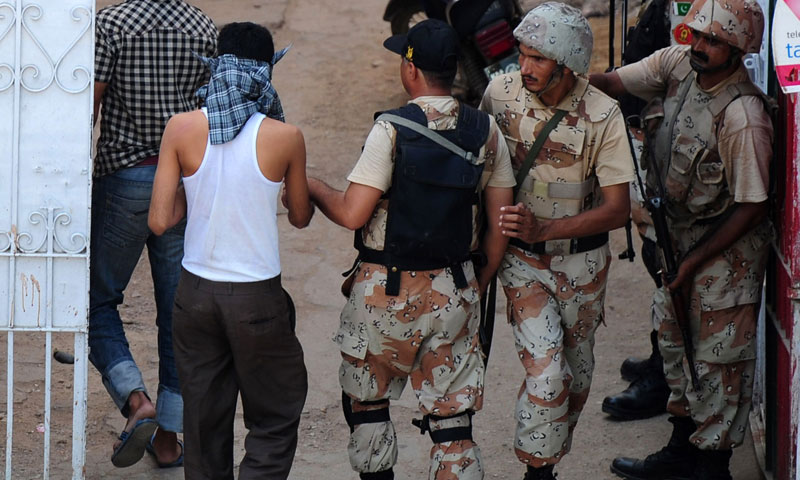 Paramilitary soldiers arrest suspects in a residential area during a targeted operation in Karachi. — Photo by AFP