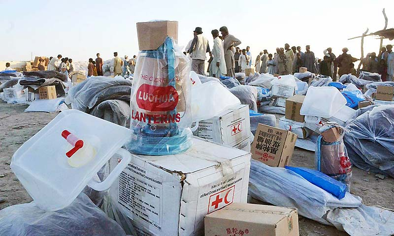 Red Crescent Pakistan officials distributing relief goods among the affectees in earthquake hit area of Dalbedi.  — Photo by APP
