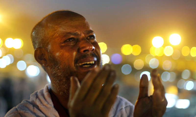 An Egyptian Muslim pilgrim cries as he prays at sunrise at Mount Arafat.—AP Photo