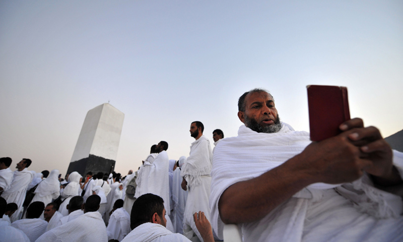 A Muslim pilgrim reads the holy Quran as he prays on top of Mount Arafat, near the holy city of Mecca. —AFP Photo