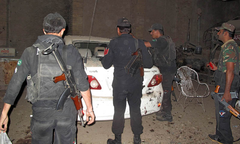 Policemen examine the site of a suicide bomb attack in Kullachi village in Dera Ismail Khan on October 16, 2013. — Photo by AFP