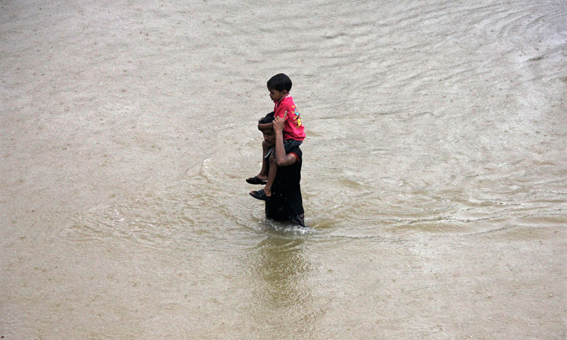 A villager carries a child through a flooded road after heavy rains at Khurda district in the eastern Indian state of Odisha October 25, 2013. — Photo by Reuters