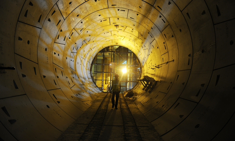 A Delhi Metro Rail Corporation employee walks through a tunnel at an underground construction site for the Janpath metro station in New Delhi. -Photo by AFP