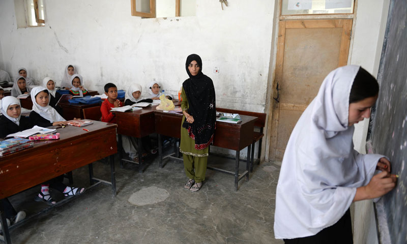 Shamsia Husseini (C) looks on as one of her students writes on the blackboard in a classroom at Mirwais Mena school in Kandahar city. — Photo by AFP