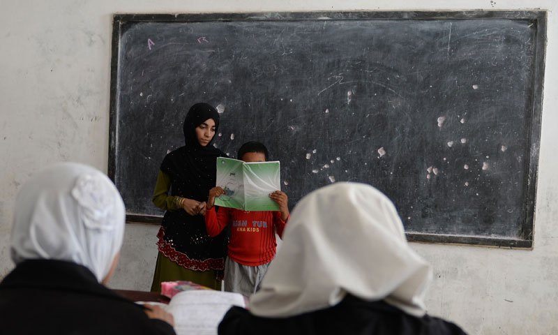 Shamsia Husseini (centre L) listens as one of her students reads his school book in a classroom at Mirwais Mena school in Kandahar city. — Photo by AFP