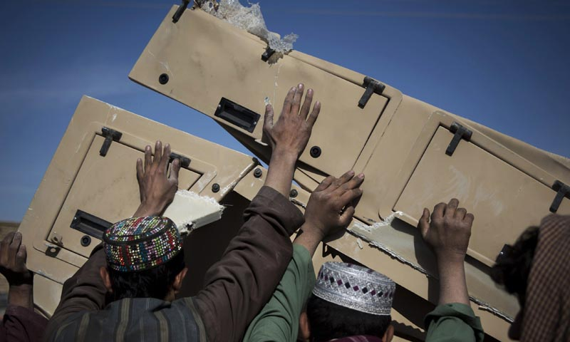 In this Saturday, Nov. 2, 2013 photo, Afghans load pieces of a destroyed US military armored vehicle into their vehicle at a junk yard in Kandahar, southern Afghanistan. — Photo by AP