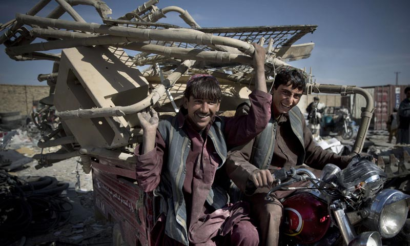 This Saturday, Nov 2, 2013 photo shows Afghan scrap collectors transport a load of destroyed US equipment from the departing military in Kandahar, southern Afghanistan. — AP
