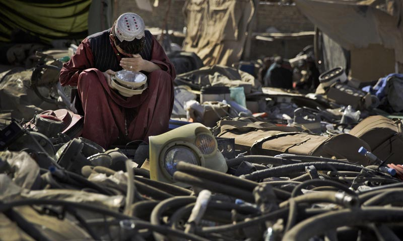 In this Saturday, Nov 2, 2013 photo, an Afghan scrap dealer checks to see if a head light bought as junk from the US military is functional a a yard in Kandahar, southern Afghanistan. — Photo by AP