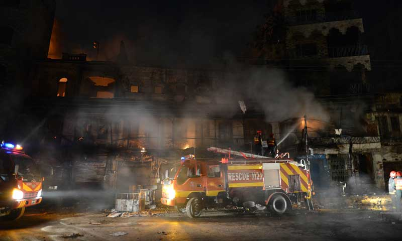 Rescuers extinguish fire at a burning market after a clash in Rawalpindi on Nov 15, 2013. — Photo by AFP