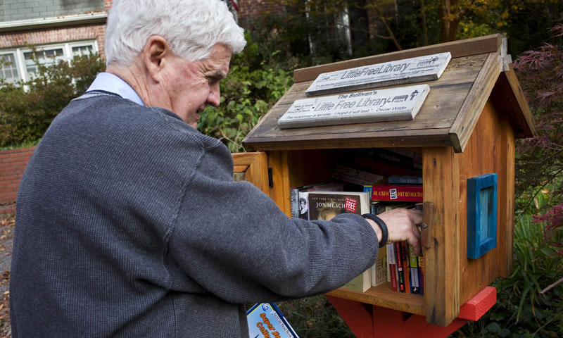 "Kevin Sullivan stands next to a ""Little Library"" book lending kiosk in front of his home in Bethesda, Maryland. — Photo by AFP"