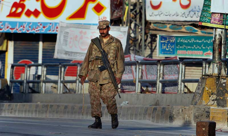 An army soldier patrols on a street during a curfew in Rawalpindi, Nov 16, 2013. — AP