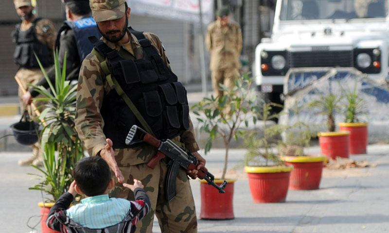A Pakistani soldier shakes hands with a child during a curfew following sectarian clashes in Rawalpindi on November 16, 2013. – AFP Photo