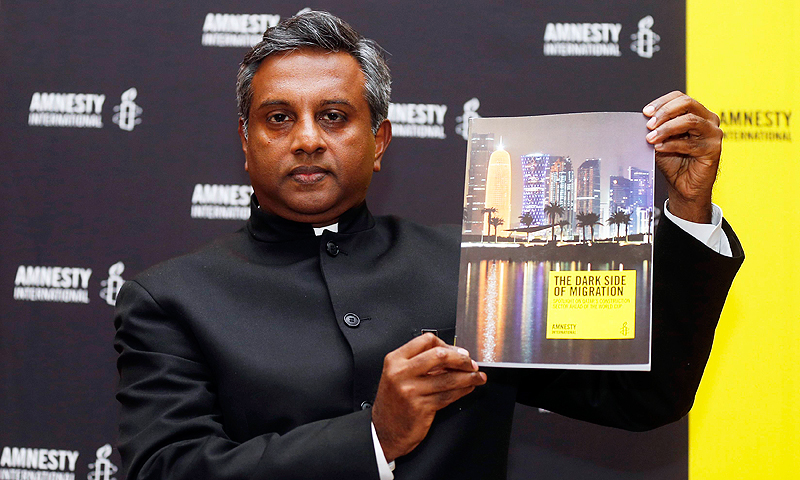 "Amnesty International Secretary General Salil Shetty holds up a report titled ""The Dark Side of Migration: Spotlight on Qatar's construction sector ahead of the World Cup"", during a news conference in Doha. -Photo by Reuters"