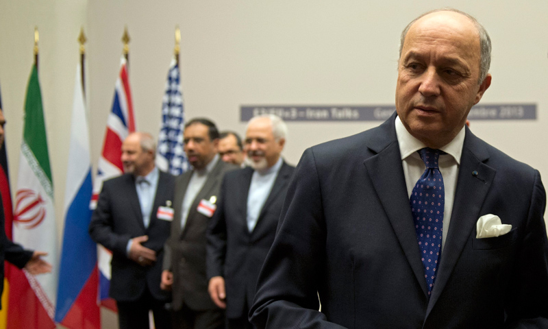 French Foreign Minister Laurent Fabius speaks to journalists next to Iranian Foreign Minister Mohammad-Javad Zarif and the Iranian delegation after the ceremony at the United Nations in Geneva, Switzerland,  Sunday, Nov.24, 2013.  —AP Photo
