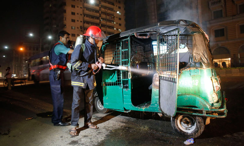 A firefighter and a policeman extinguish a fire on an auto rickshaw in Dhaka. Supporters of  BNP led opposition parties blast crude bombs, vandalised and set fire on vehicles after the announcement of 10th parliamentary election schedule on Monday, local media reported. — Photo by Reuters
